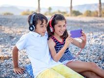 Os adolescentes sentam-se na praia com fones de ouvido olham o telefone imagens de stock royalty free