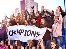Os aficionados desportivos mantêm a bandeira do campeão em tribunas Imagens de Stock Royalty Free
