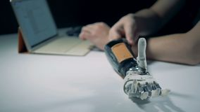 Os ajustes de um braço mecânico estão sendo regulados de um portátil video estoque
