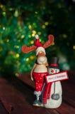 os alces e o boneco de neve com um cumprimento assinam o Feliz Natal em um de madeira Fotos de Stock Royalty Free