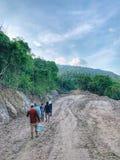 Os aldeões estão andando na estrada de terra a sua vila no do sul de Tailândia fotografia de stock royalty free