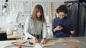 Os alfaiates novos estão trabalhando com tabuleta, estão comunicando e estão esboçando o teste padrão da roupa na matéria têxtil  video estoque
