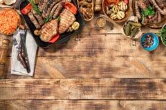 Os alimentos diferentes cozinharam na grade na tabela de madeira Imagens de Stock Royalty Free