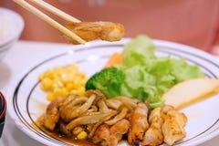 Os alimentos, a galinha de Teriyaki e os cogumelos japoneses serviram com salada usando hashis para escolher uma parte de galinha imagem de stock royalty free