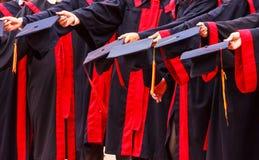 Os alunos diplomados guardam chapéus nas mãos na cerimônia do sucesso da graduação da universidade Felicitações no sucesso da edu foto de stock royalty free