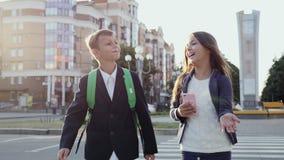 Os alunos estão andando ao longo da rua da cidade vídeos de arquivo