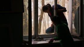 Os alunos lavam as janelas de madeira na sala de aula em sua escola home video estoque