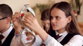 Os alunos na farda da escola estão estudando a disposição do ADN que senta-se na sala de aula vídeos de arquivo