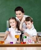 Os alunos pequenos estudam a química na classe do laboratório Foto de Stock