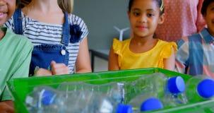 Os alunos que põem garrafas reciclam dentro o recipiente na mesa na sala de aula 4k video estoque