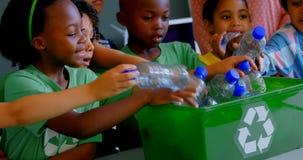 Os alunos que p?em garrafas reciclam dentro o recipiente na mesa na sala de aula 4k vídeos de arquivo