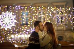 Os amantes beijam no fundo de brilhar festões festivas foto de stock