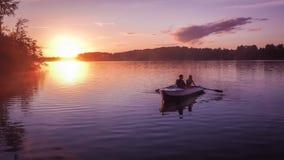 Os amantes bonitos da data pequena loving dourada romântica do barco de enfileiramento dos pares da névoa do lago do rio do por d Fotos de Stock Royalty Free