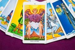 Os amantes, cartões de Tarot em um roxo da tabela. Imagem de Stock