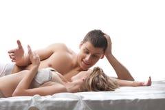 Os amantes dos pares falam e sorriem na cama Imagens de Stock Royalty Free