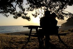 Os amantes equipam e mulher que beija em uma praia Imagem de Stock