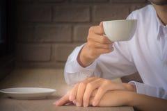 Os amantes estão bebendo o café ao guardar as mãos fotografia de stock royalty free