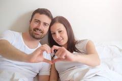 Os amantes felizes acoplam o encontro confortável de sentimento na cama foto de stock royalty free