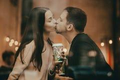 Os amantes felizes indiv?duo e menina est?o beijando na soleira em um caf? e est?o guardando copos em suas m?os imagens de stock