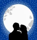 Os amantes mostram em silhueta o beijo no luar Fotografia de Stock Royalty Free