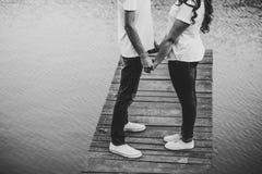 Os amantes novos emparelham-se, guardado das mãos em uma ponte de madeira perto do lago r fotos de stock royalty free