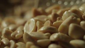 Os amendoins descascados são fritados em uma bandeja Mão com uma colher que agita porcas filme