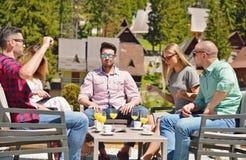 Os amigos à moda bonitos estão usando uma tabuleta digital, café bebendo e estão sorrindo ao descansar no parque imagens de stock
