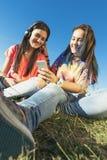 Os amigos adolescentes felizes no verão estacionam a música de escuta Fotos de Stock Royalty Free