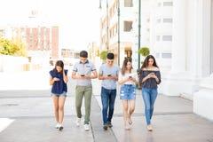 Os amigos agrupam com telefone que andam fora imagens de stock royalty free