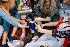 Os amigos agrupam obtêm mornos com chá na barraca imagens de stock royalty free