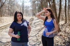 Os amigos aptos e excessos de peso das mulheres bebem a água e o resto após o jogg Fotos de Stock Royalty Free