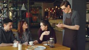 Os amigos atrativos estão pedindo o alimento e as bebidas no café quando o garçom de sorriso amigável no avental escrever a ordem filme