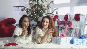 Os amigos bonitos novos colocam em um tapete perto do abeto do Natal e para beber Champagne para relaxar pela janela Movimento le video estoque