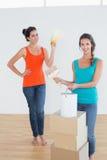 Os amigos com caixas, escova e pintura podem escolhendo a cor Imagens de Stock Royalty Free