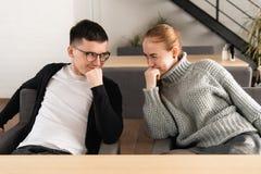 Os amigos com olhar conspirativo sentam-se na frente de se e fazendo um plano foto de stock