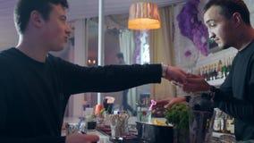 Os amigos com resto das bebidas perto da barra estão, homem novo dão o dinheiro ao empregado de bar para um cocktail video estoque