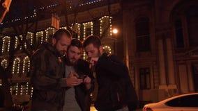Os amigos com um smartphone estão procurando um lugar na cidade da noite O grupo de turistas foi perdido vídeos de arquivo