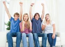 Os amigos comemoram junto ao sentar-se Imagem de Stock Royalty Free