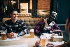 Os amigos consideráveis são cerveja da bebida e sorriso ao descansar no bar imagens de stock