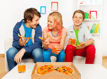 Os amigos de sorriso felizes comem junto a pizza em casa Fotografia de Stock Royalty Free