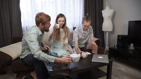 Os amigos dois indivíduos, irmãos, e uma jovem mulher estão sentando-se na casa e no chá bebendo, comendo o bolo de queijo Amigos video estoque