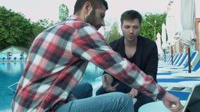 Os amigos dos homens de negócios comunicam-se pela associação que senta-se em deckchairs Um homem novo diz a seu amigo-colega uma filme