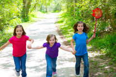 Os amigos e as meninas da irmã que correm na floresta seguem feliz Imagens de Stock