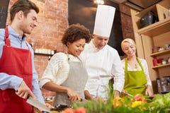 Os amigos e o cozinheiro chefe felizes cozinham o cozimento na cozinha Imagens de Stock Royalty Free
