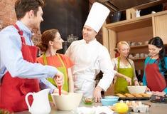 Os amigos e o cozinheiro chefe felizes cozinham o cozimento na cozinha Imagens de Stock
