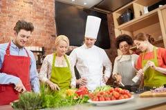 Os amigos e o cozinheiro chefe felizes cozinham o cozimento na cozinha Foto de Stock