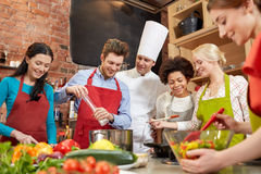 Os amigos e o cozinheiro chefe felizes cozinham o cozimento na cozinha Fotos de Stock