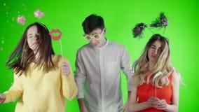 Os amigos estão dançando em um confete colorido em uma tela verde vídeos de arquivo