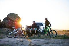 Os amigos estão descansando no caminhão Offroad do recolhimento após a bicicleta que monta nas montanhas no por do sol Conceito d imagens de stock