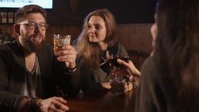 Os amigos estão falando em uma barra e em umas bebidas misturadas bebendo na noite video estoque
